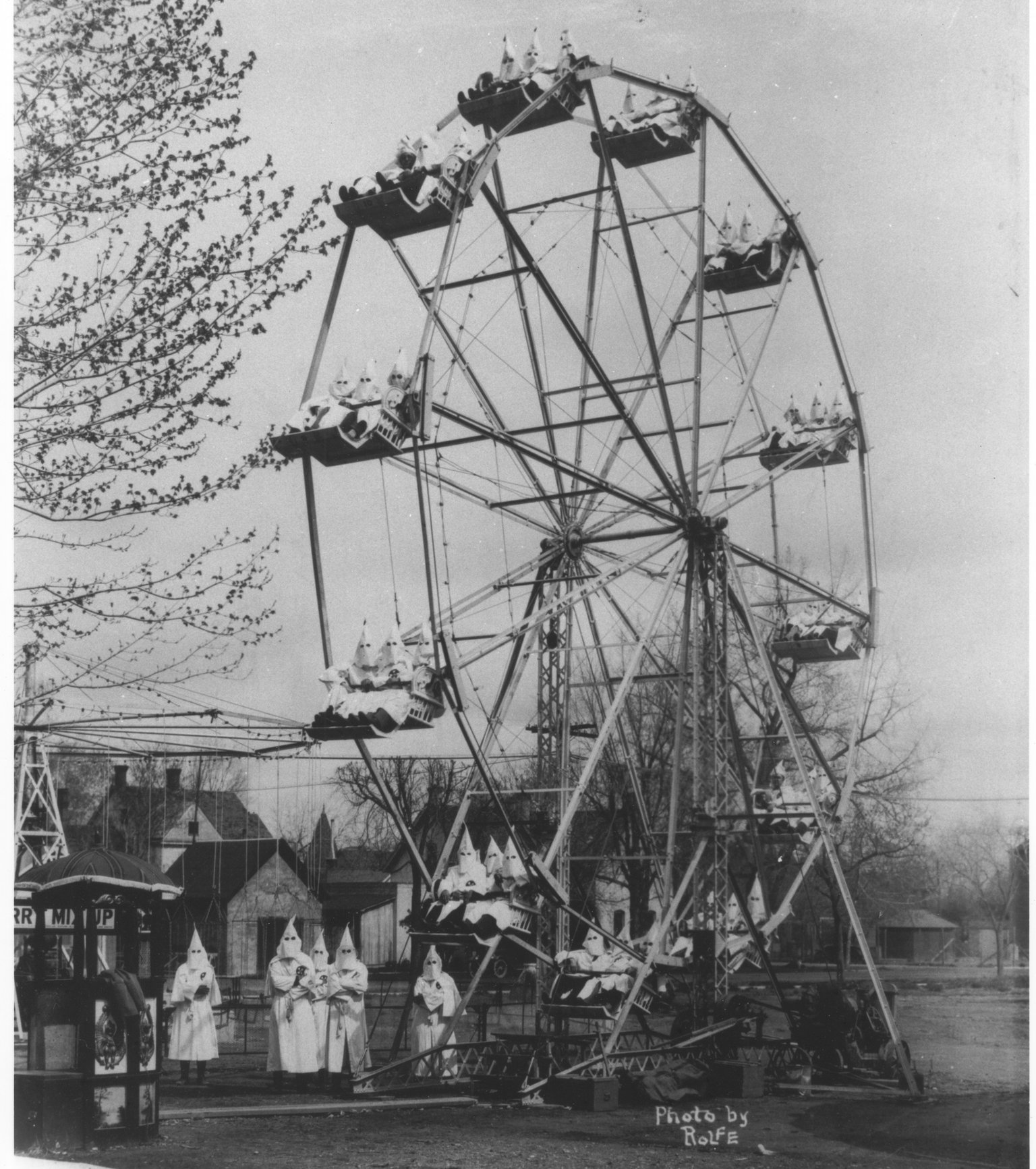 Robed Klan members ride three to a seat on a Ferris wheel while additional robed members stand at the base of the ride.